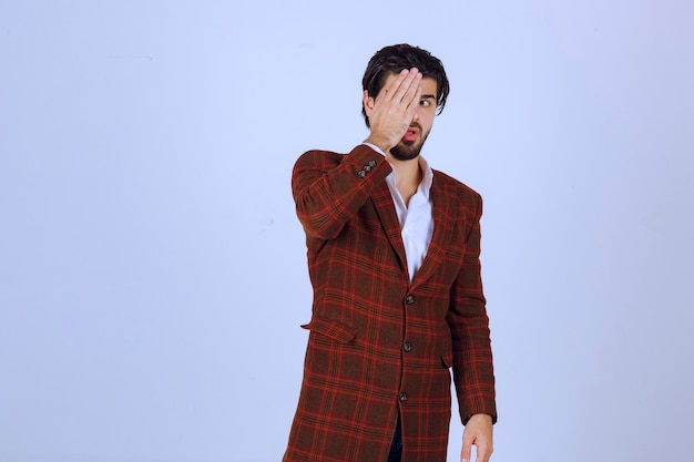 手で顔を隠している茶色のジャケットの男。