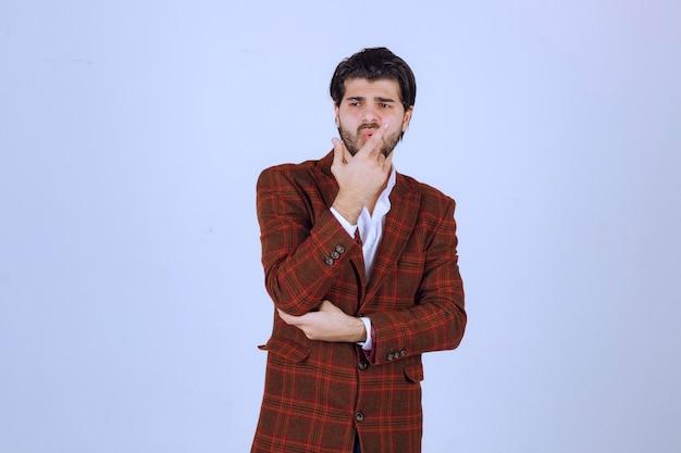 茶色のジャケットを着た男は、思慮深く、混乱し、迷子に見えます。 無料写真
