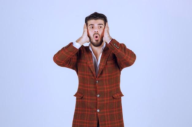 茶色のジャケットを着た男は、思慮深く、混乱し、迷子に見えます。