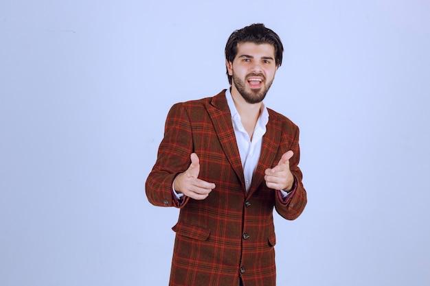 良い手サインを作る茶色のジャケットの男。