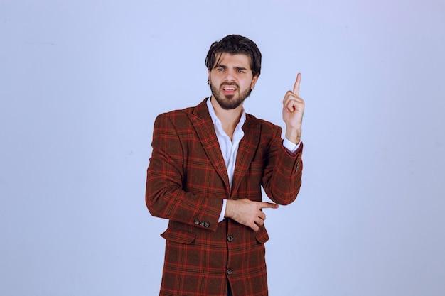 Человек в коричневой куртке указывая вверх и что-то представляя.