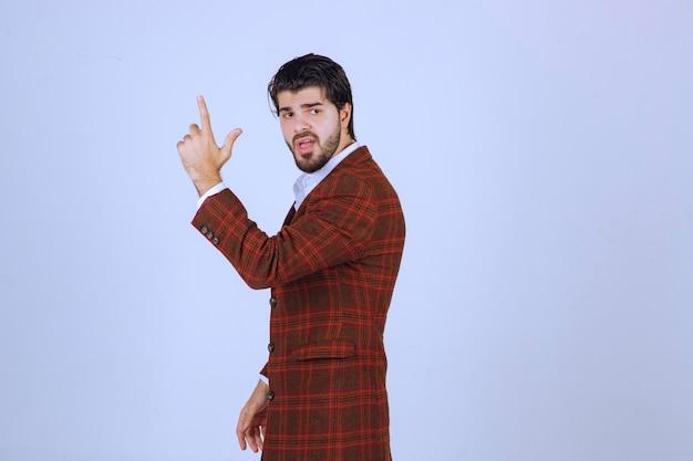注意のために手を上げる茶色のジャケットの男。