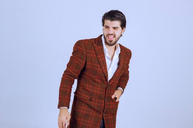 Человек в коричневой куртке стоит и смотрит без реакции.