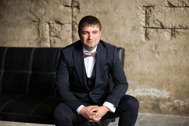 Человек в деловом костюме и галстуке-бабочке на диване