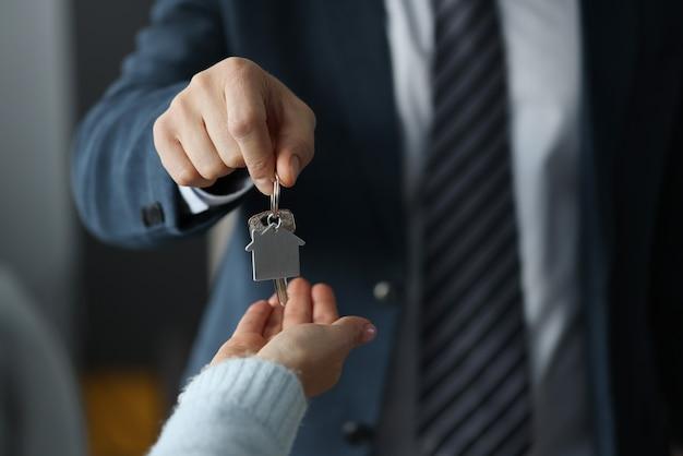 ビジネススーツを着た男性が家の鍵を女性のクローズアップに渡す