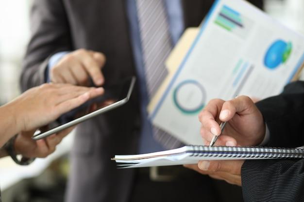 手に紙を持つビジネススーツの男は同僚とボールペンで書く