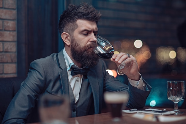 アルコールひげを生やした男を飲むカフェの男は、クラブで長いひげを飲んでパブのビジネスマンで待っているワイングラス完璧なワインだけでヒップスターとレストランで休む