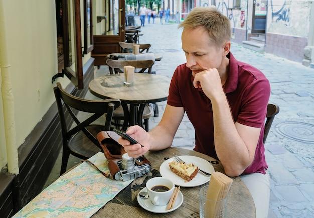 Мужчина в кафе держит смартфон