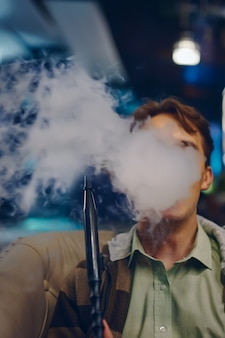 Мужчина в кафе курит кальян густой дым от кальяна молодой парень на диване в ресторане цветные огни на б ...
