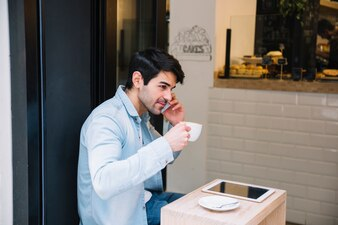Man in cafe talking on phone
