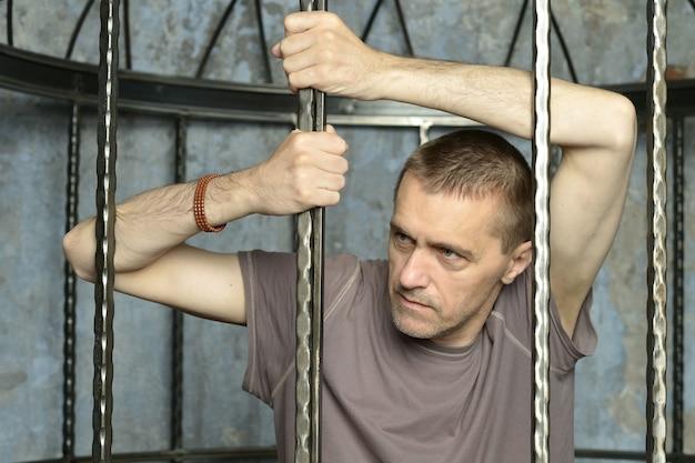 Человек в клетке с руками на стальной решетке