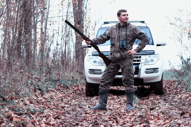 Человек в камуфляже и с охотничьим ружьем в лесу на весенней охоте