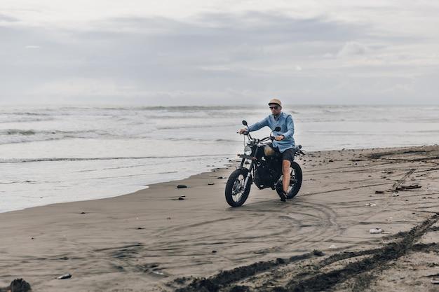 ビーチでバイクに乗ってキャップの男。バリ島のビーチサンセットでモトクロスダートバイカー。自由とアクティブなライフスタイルを楽しんで、バイカーツアーを楽しんでいる若い流行に敏感な男性。