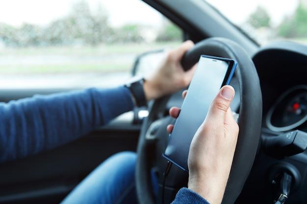 차에있는 남자는 스마트 폰을 사용하고 있습니다. 승차 공유, 운전 안전 또는 gps 내비게이션의 개념.