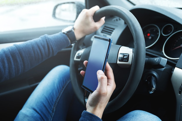 車の中で男はスマートフォンを使用しています。ライドシェアリング、運転の安全性、またはgpsナビゲーションの概念。
