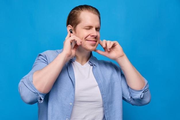 目を閉じて青のカジュアルな服装の男がワイヤレスヘッドフォンを耳に押し込み、一緒に歌います。