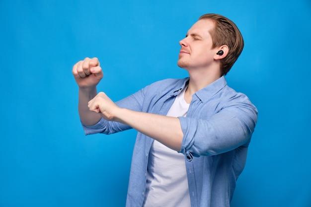目を閉じて青にカジュアルな服装の男は、ワイヤレスヘッドフォンで音楽を聴き、踊ります。