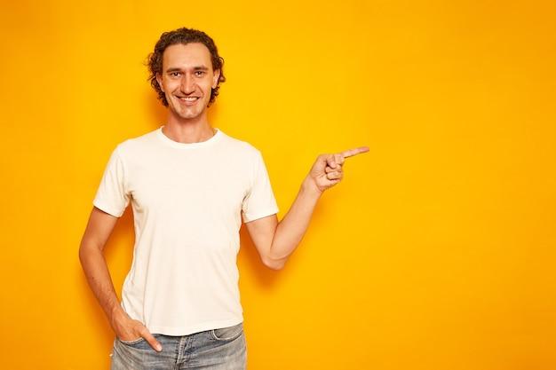 カジュアルな服装の男は、黄色の背景で隔離の空の領域に人差し指で指しています