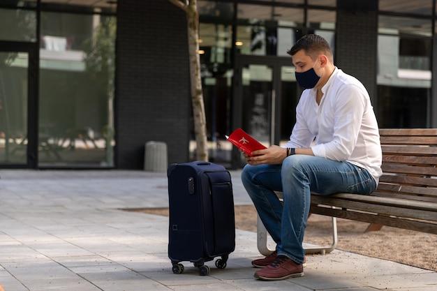 Человек в повседневной одежде сидит на скамейке с багажом