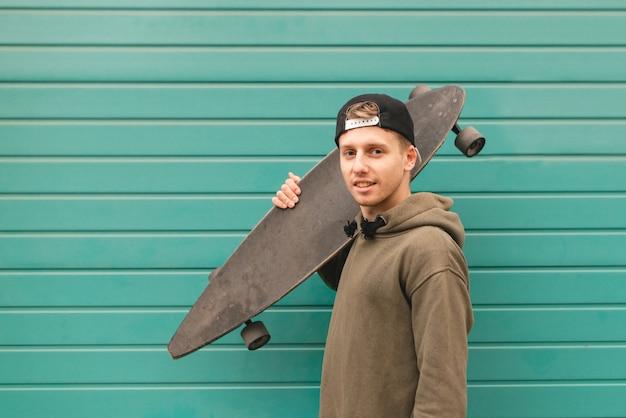 Человек в повседневной одежде стоит с longboard в руках на бирюзовом фоне и смотрит на камеру.