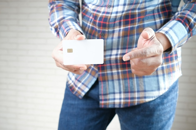 신용 카드를 보여주는 캐주얼 드레스 남자