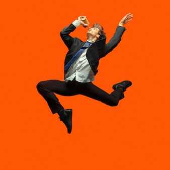 Человек в повседневной офисной одежде прыгает и танцует изолирован на ярко-оранжевом