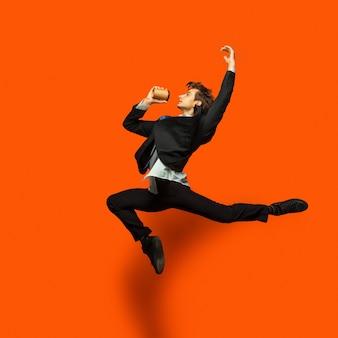 Человек в повседневной офисной одежде прыгает и танцует, изолирован на ярко-оранжевом
