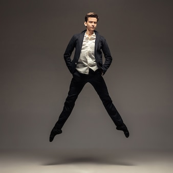 Человек в повседневной офисной одежде прыгает и танцует изолирован на сером