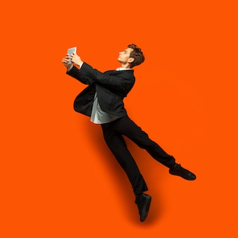 カジュアルなオフィススタイルの服を着た男が壁に孤立してジャンプ