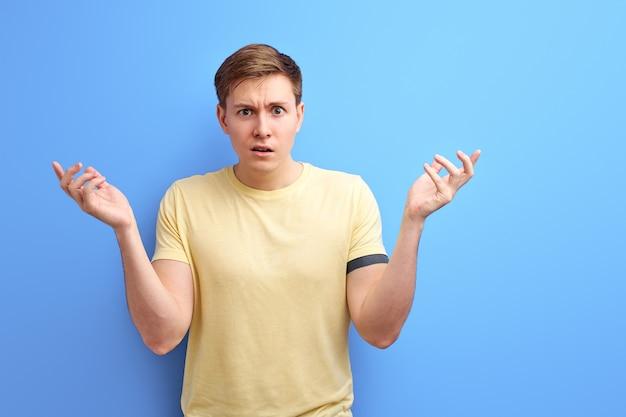 孤立した青い背景の上に立っているカジュアルなtシャツの男は無知で混乱し、考えも疑わしい顔も肩をすくめます。彼は何かや誤解を知りません