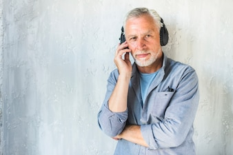 Man in casual wear listening music on headphone standing against concrete wall