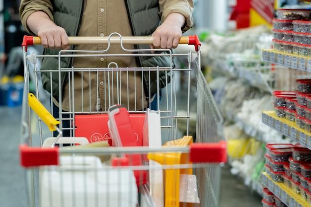 Мужчина в повседневной одежде толкает тележку для покупок во время посещения супермаркета