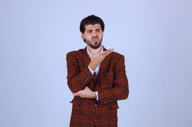 シーンでスピーチをし、上に何かを提示しているチェックブレザーの男。 無料写真