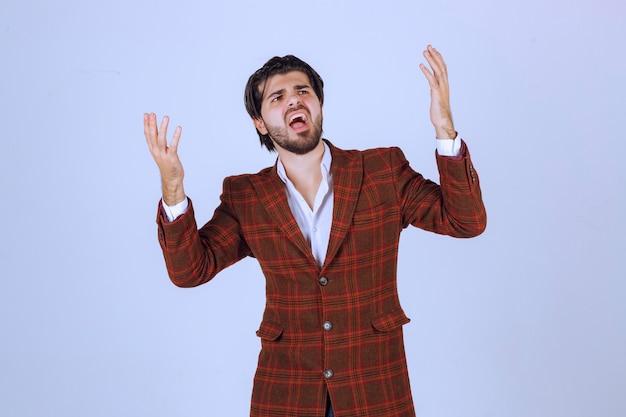 シーンでスピーチをし、上に何かを提示しているチェックブレザーの男。