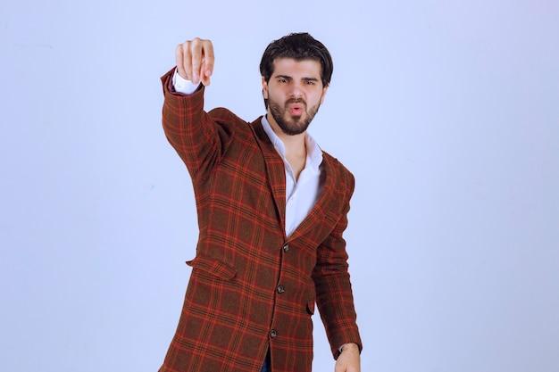 何かにスパイスを加えるチェックジャケットの男。