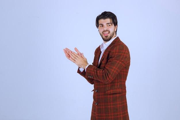 체크 재킷을 입은 남자가 무언가 또는 누군가에게 박수를 보냅니다. 고품질 사진