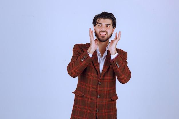 Мужчина в клетчатой куртке аплодирует кому-то или чему-то.