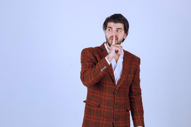 チェックジャケットを着た男が口を見せて沈黙を求めている。