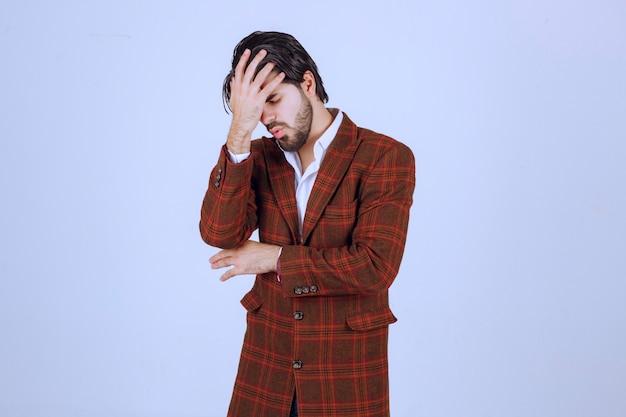 チェックのジャケットを着た男は、何かについてとても悲しくて泣いています。