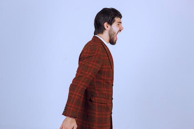チェックのジャケットを着た男は、何かについてとても悲しくて泣いています。 無料写真