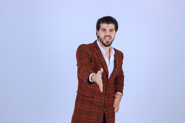 체크 재킷을 입은 남자가 손을 흔들어 누군가를 맞이합니다.