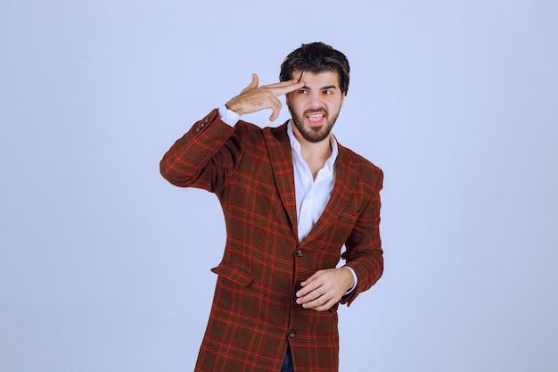 누군가를 기대하는 체크 재킷을 입은 남자.