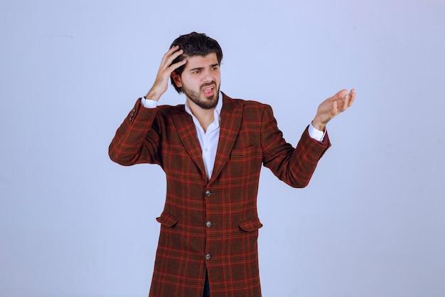 Мужчина в клетчатой куртке выглядит растерянным и неопытным.