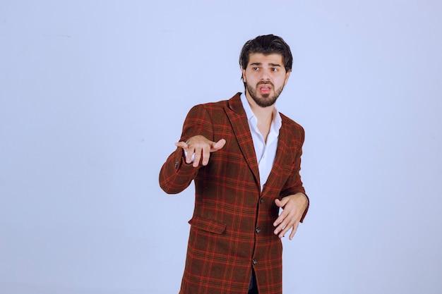 체크 재킷을 입은 남자는 혼란스럽고 경험이 없어 보입니다.