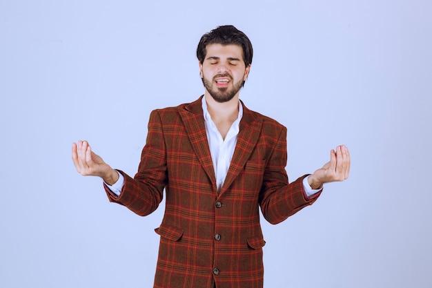 Человек в клетчатой куртке делает медитацию.