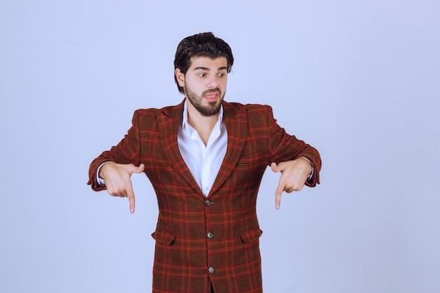 チェックジャケットを着た男が指で下を向いて何かを見せている。