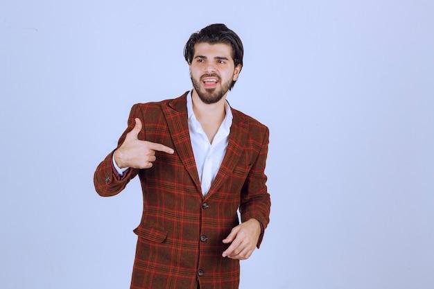 チェックジャケットを着た男が自分を指差して演じています。