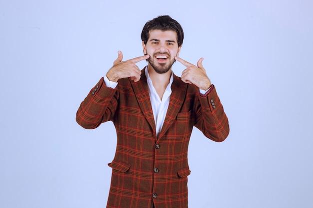 그의 입을 가리키고 미소를 요구하는 체크 재킷을 입은 남자.
