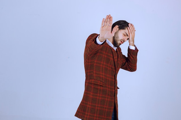 체크 재킷을 입은 남자가 두통이나 피곤함으로 고개를 갸웃합니다.