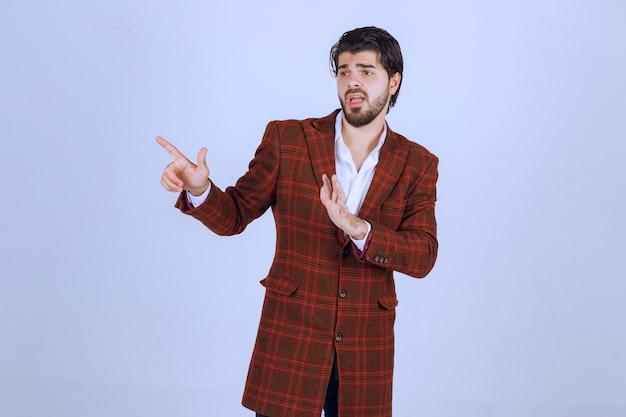 체크 재킷을 입은 남자가 손짓으로 누군가를 막습니다.